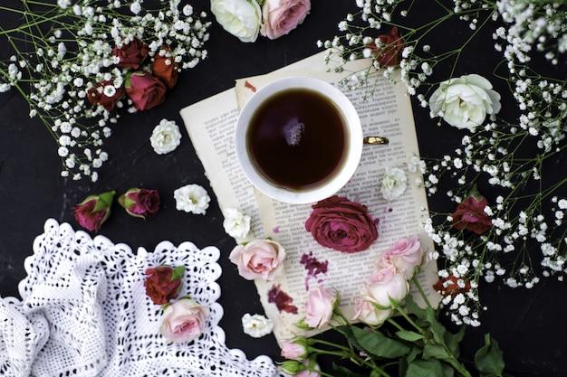 Een top close-up hete thee kopje thee samen met kleurrijke rozen op het donkere oppervlak Gratis Foto