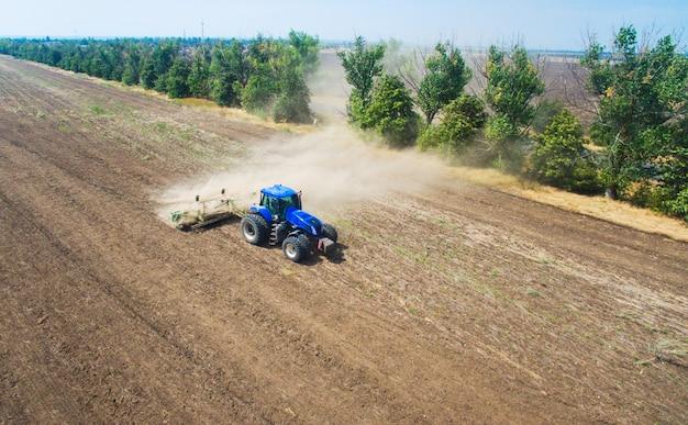 Een tractor die en in het gebied ploegt zaait Premium Foto