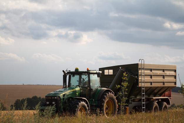 Een tractor voor het verzamelen van tarwe uit een maaidorser staat op een veld van gemaaide tarwe tegen een blauwe bewolkte hemel Premium Foto