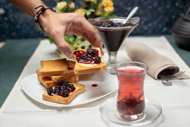 Een traditioneel armudu-glas zwarte thee met toast met aardbeienjam. een persoon die proost. Gratis Foto