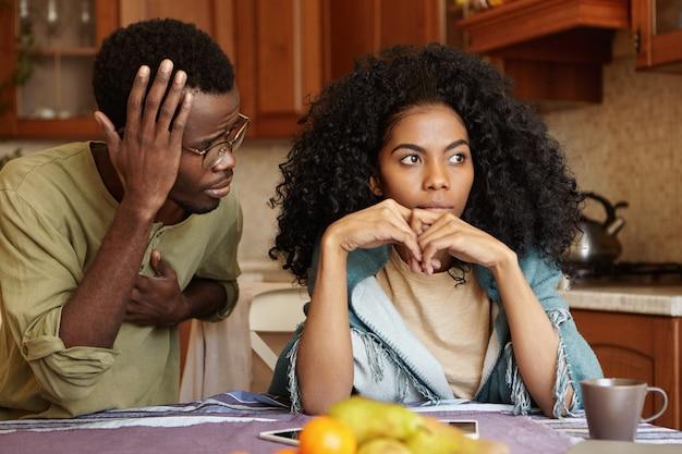 Een trieste teleurgestelde vrouw kan haar man niet vergeven voor ontrouw die naast haar zit en haar verontschuldigende blik schuldig maakt en zegt dat het een vergissing was. african american paar geconfronteerd met relatieproblemen Gratis Foto