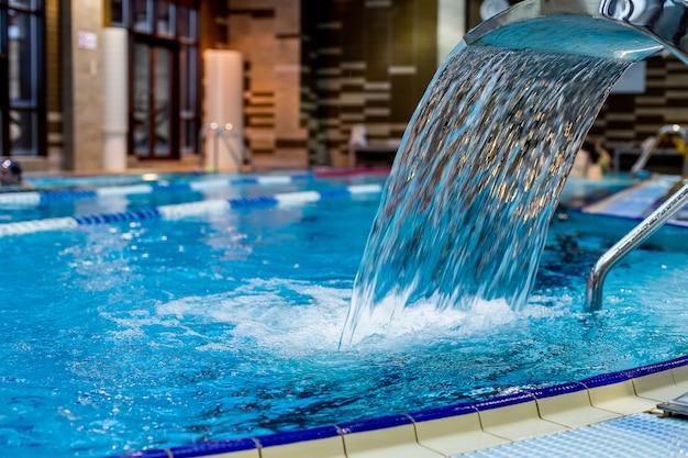 Een turquoise waterval, rug- en schoudermassage in het zwembad. Premium Foto