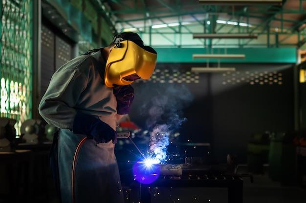 Een vakman is aan het lassen met werkstukstaal. werkende persoon over lasserstaal gebruik van elektrische lasmachine er komen lichtlijnen uit en veiligheidsuitrusting in de fabrieksindustrie. Premium Foto