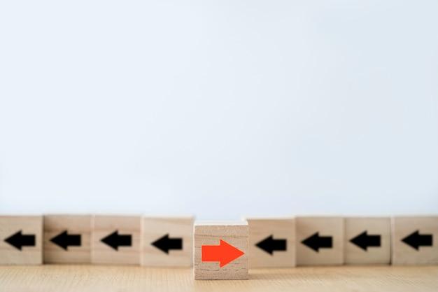 Een van de rode pijlen beweegt in de tegenovergestelde richting met andere zwarte pijlen die op houten blokblokjes zijn gesneden Premium Foto