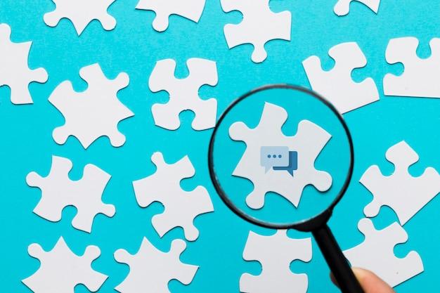 Een vergrootglas van de persoonsholding over het berichtpictogram op witte raadsel tegen blauwe achtergrond Gratis Foto