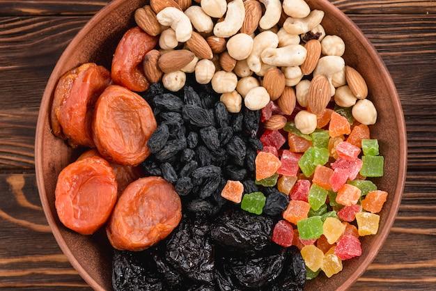 Een verhoogde weergave van abrikoos; gedroogd fruit; zwarte rozijnen en noten in kom op houten oppervlak Gratis Foto