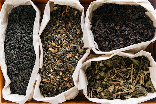 Een verhoogde weergave van assortiment van droge thee in papieren zak Gratis Foto