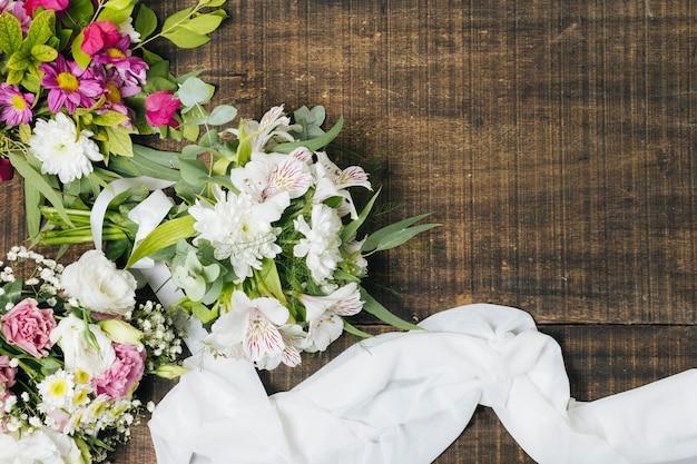 Een verhoogde weergave van bloemboeket met witte sjaal op houten tafel Gratis Foto