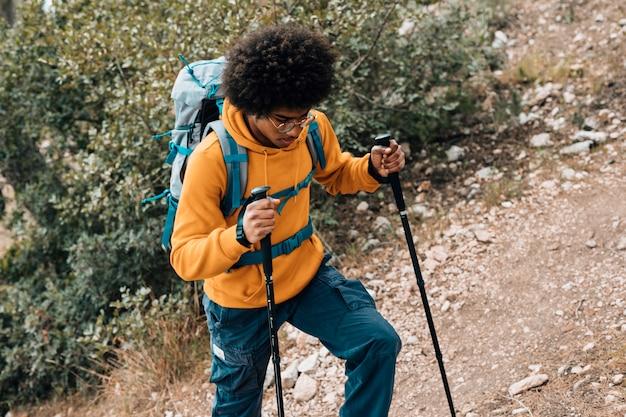 Een verhoogde weergave van een afrikaanse jonge man wandelen in de bergen Gratis Foto