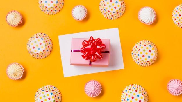 Een verhoogde weergave van geschenkdoos op wit papier met aalaw en polka dot papieren cakevormen op gele achtergrond Gratis Foto