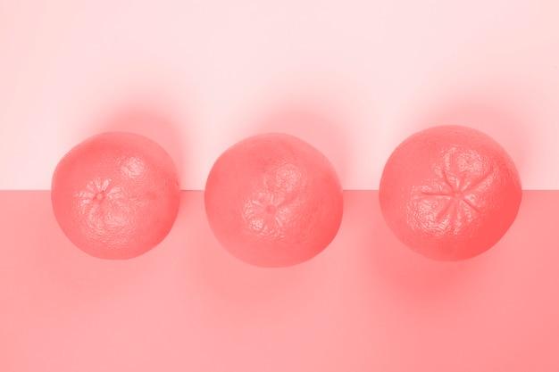 Een verhoogde weergave van hele drie grapefruit op roze achtergrond Gratis Foto