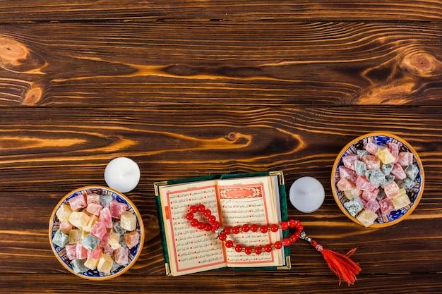 Een verhoogde weergave van kaarsen; rode gebedsparels met heilige kuran en lukum-kommen op houten lijst Gratis Foto