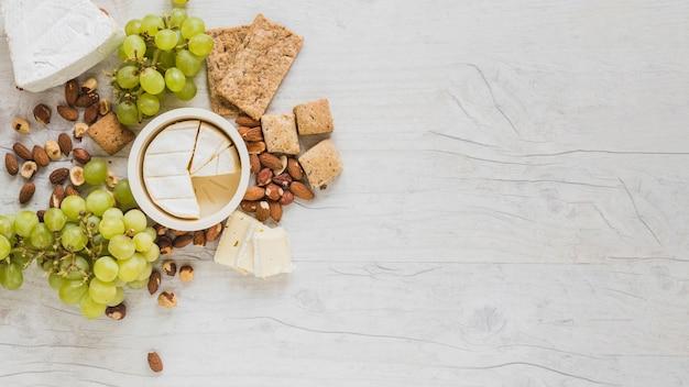 Een verhoogde weergave van kaasblokjes, druiven, gedroogde vruchten en crackers op grijs houten bureau Gratis Foto