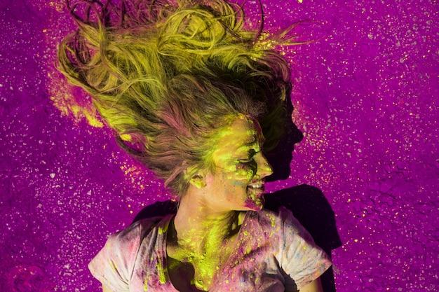 Een verhoogde weergave van lachende vrouw bedekt met holi kleur poeder Gratis Foto