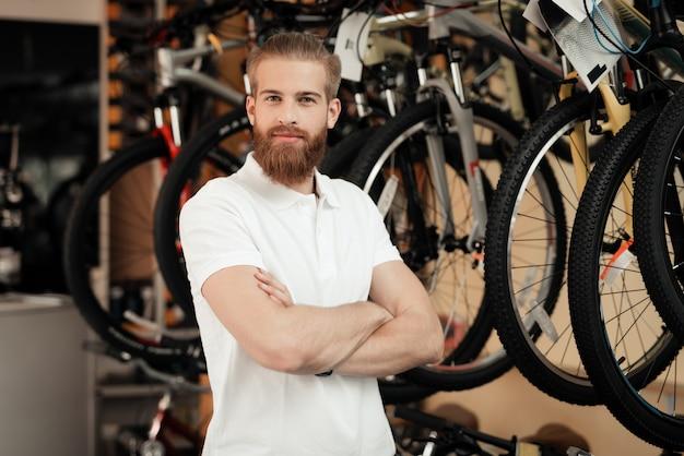 Een verkoper in een fietsenwinkel poseert in de buurt van een fiets. Premium Foto