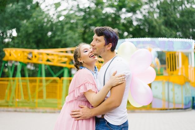 Een verliefd paar in lichte kleding omhelzen elkaar, een meisje houdt ballonnen in haar handen, ze glimlachen en zijn blij Premium Foto