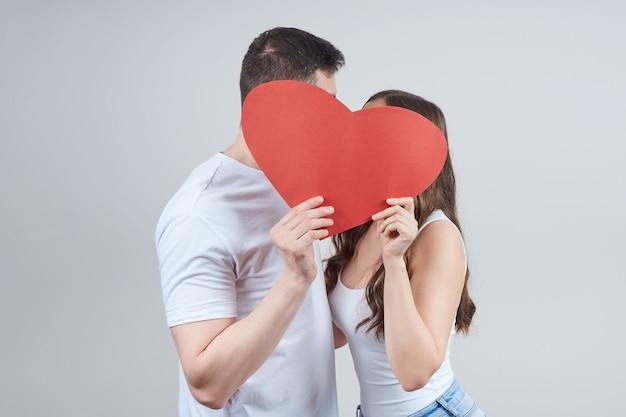 Een verliefd stel houdt een papieren rood hart vast, dat hun gezichten bedekt. fijne valentijnsdag. Premium Foto
