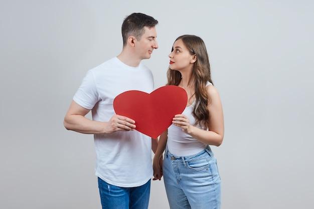 Een verliefd stel houdt een papieren rood hart vast, kijk elkaar aan. fijne valentijnsdag. Premium Foto