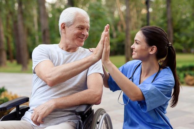 Een verpleegster en een oude man in een rolstoel high five. Premium Foto