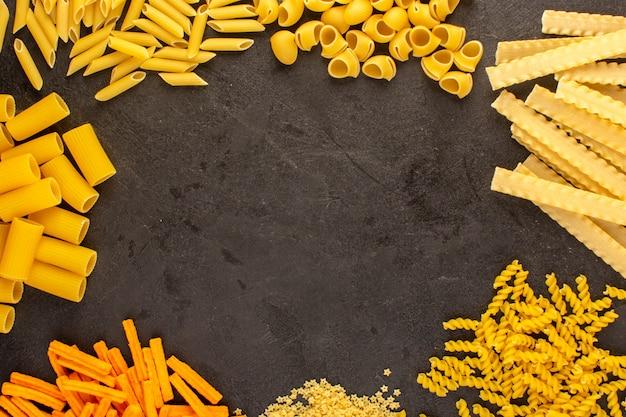 Een verschillende bovenaanzicht gele rauwe pasta vormde geïsoleerd weinig en lang op de donkere spaghetti van italiaans van het achtergrondmaaltijdvoedsel Gratis Foto