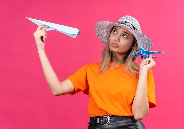 Een verwarde, mooie jonge vrouw in een oranje t-shirt met een zonnehoed op een vliegend papieren vliegtuigje terwijl ze een blauw speelgoedvliegtuig op een roze muur vasthoudt Gratis Foto