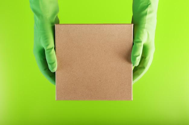 Een vierkante doos in de handen met groene rubberen handschoenen op een groene achtergrond. Premium Foto