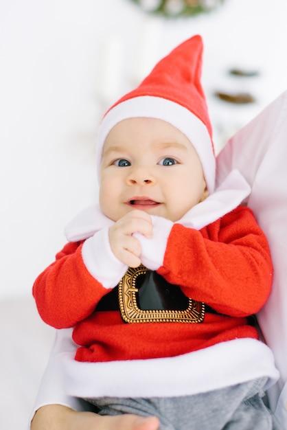 Een vijf maanden oud klein kind in een pak van de kerstman ligt in de handen van de ouders Premium Foto