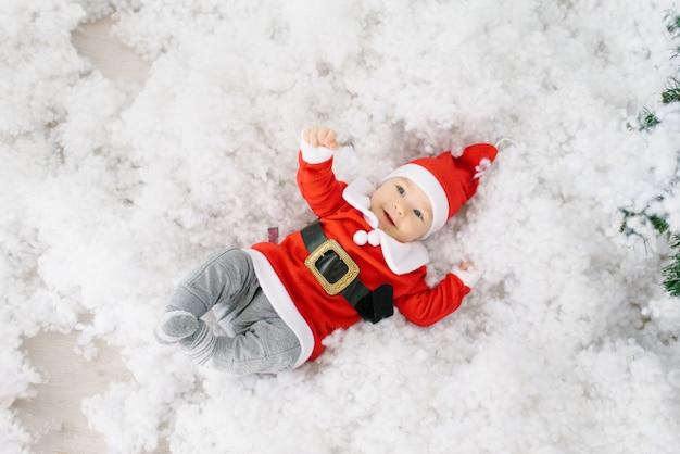 Een vijf maanden oud klein kind in een pak van de kerstman ligt in kunstmatige sneeuw op zijn rug Premium Foto