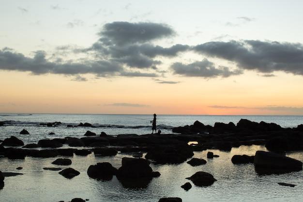 Een visser vist in de zwarte stenen in de oceaan. Premium Foto