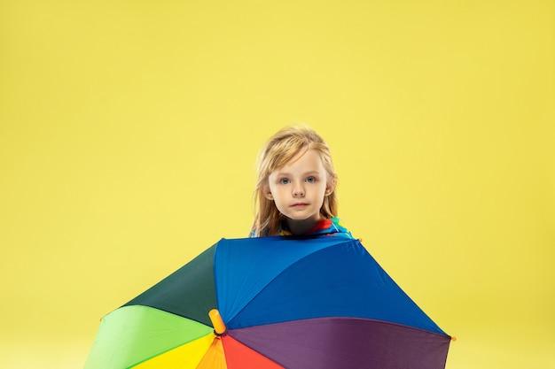 Een volledig lengteportret van een helder modieus meisje met regenboogparaplu Gratis Foto