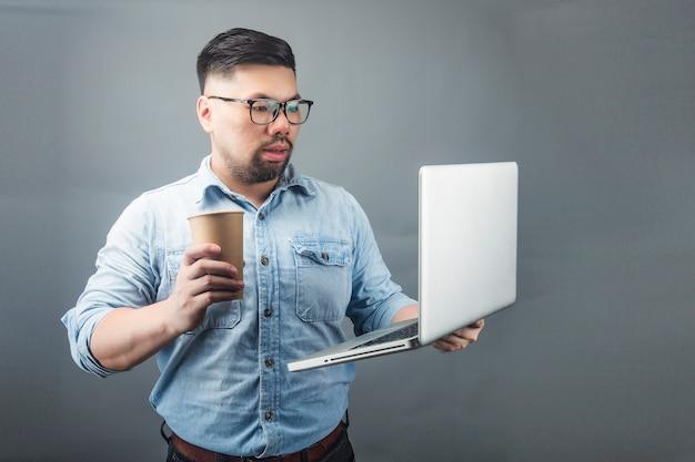 Een volwassen man met een computer en koffie Premium Foto