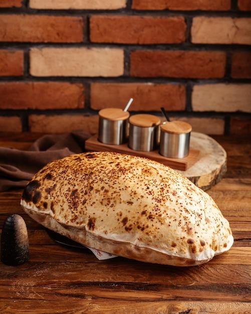 Een vooraanzicht bakte brood heet en vers op het bruine houten bureau Gratis Foto