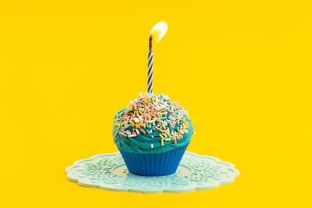 Een vooraanzicht blauwe cake met kleurrijke kleine snoepjes en kaars op gele, kleur koekjessuiker Gratis Foto