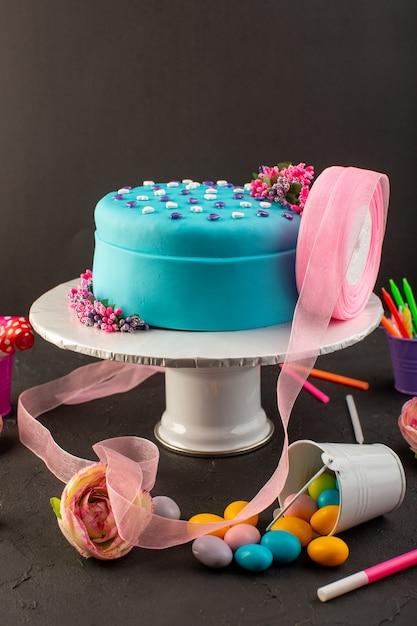 Een vooraanzicht blauwe verjaardagstaart met snoepjes en kaarsen op de donkere partij van de de cakeviering van de bureauverjaardag Gratis Foto
