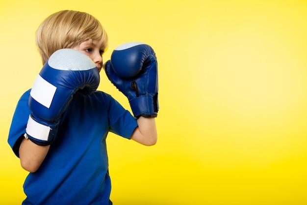 Een vooraanzicht blonde jongen poseren boksen in blauwe bokshandschoenen op de gele muur Gratis Foto