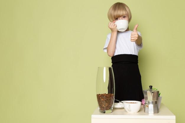 Een vooraanzicht blonde jongen schattig zoete koffie drinken in wit t-shirt op de steen gekleurde bureau Gratis Foto