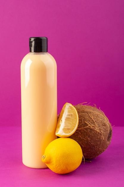 Een vooraanzicht crème gekleurde fles plastic shampoo kan met zwarte dop samen met citroenen en kokos geïsoleerd op de paarse achtergrond cosmetica schoonheid haar Gratis Foto