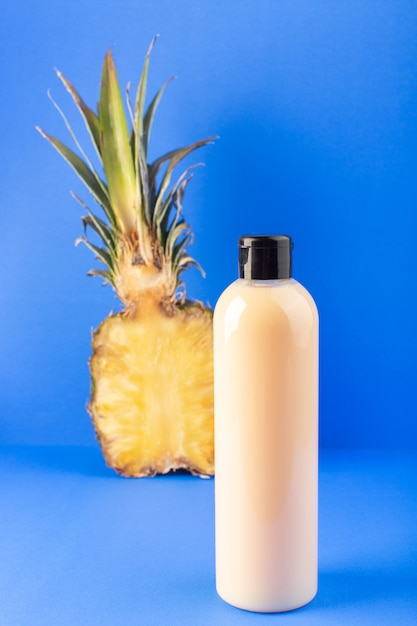 Een vooraanzicht crèmekleurige fles plastic shampoo kan met zwarte dop geïsoleerd samen met gesneden ananas op de blauwe achtergrond cosmetica schoonheid haar Gratis Foto