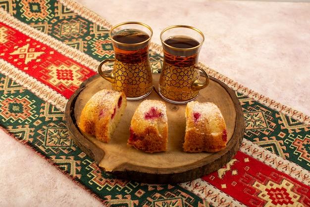 Een vooraanzicht gebakken fruitcake heerlijk gesneden met rode kersen binnen en suikerpoeder op houten bureau met thee op roze Gratis Foto