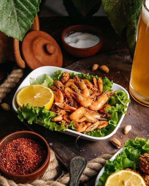 Een vooraanzicht gebakken garnalen met citroen en groene salade op tafel voedsel maaltijd zeevruchten kanker Gratis Foto