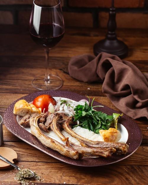 Een vooraanzicht gebakken vleesbeenderen met greens en tomaat op het bruine houten het voedselvlees van de bureaumaaltijd Gratis Foto