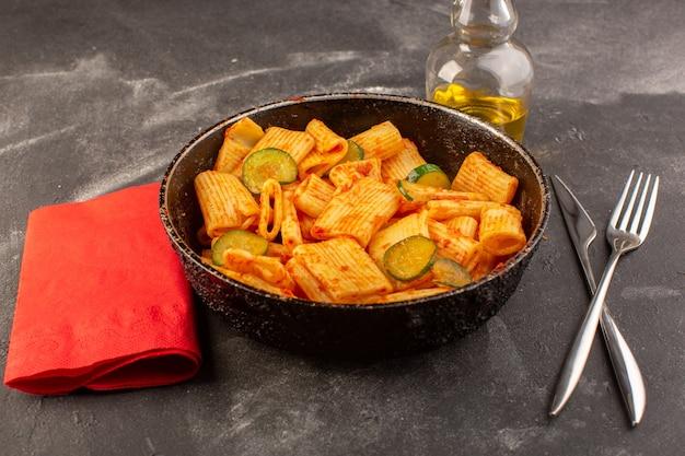 Een vooraanzicht gekookte italiaanse pasta met tomatensaus en komkommer in de pan op het donkere oppervlak Gratis Foto