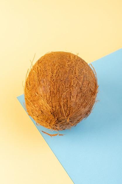 Een vooraanzicht gesloten kokosnoten hele melkachtig fris mellow geïsoleerd op de crème-iced-blauw gekleurde achtergrond tropische exotisch fruit moer Gratis Foto