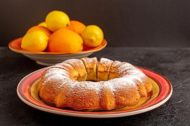 Een vooraanzicht gesloten zoete ronde cake met suikerpoeder gesneden zoete heerlijke geïsoleerde cake binnen plaat samen met citroenen en grijze achtergrond koekje suiker koekje Gratis Foto