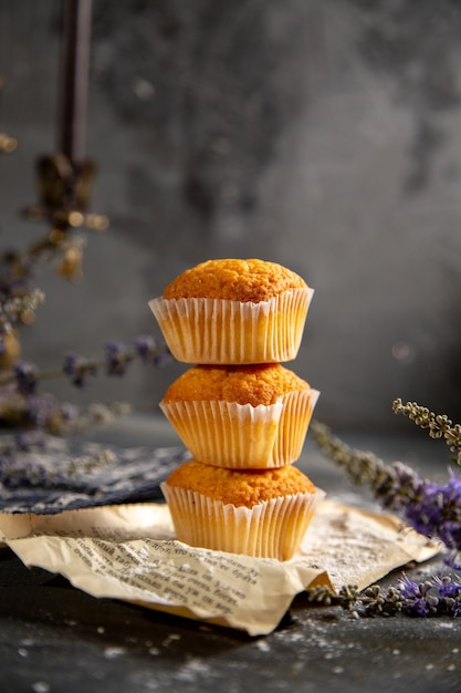 Een vooraanzicht heerlijke kleine cakes met paarse bloemen op de grijze tafel koekjes thee koekje zoet Gratis Foto