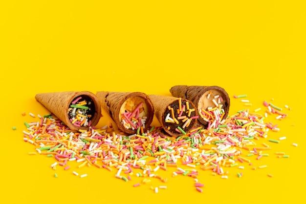 Een vooraanzicht-ijshoorns met gekleurde snoepdeeltjes op gele, hoorn zoete suikerkleur Gratis Foto