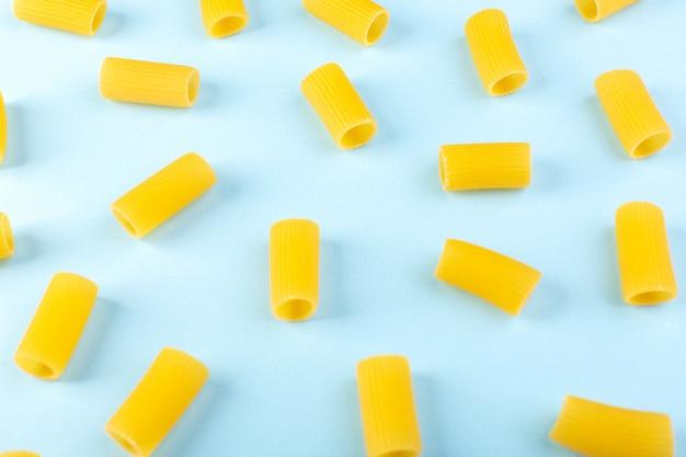 Een vooraanzicht isoleerde gele weinig ruw deegwaren op de blauwe de spaghettideegwaren van de achtergrondvoedselmaaltijd Gratis Foto