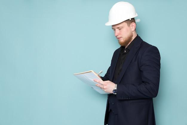 Een vooraanzicht jong aantrekkelijk mannetje met baard in zwart donker klassiek modern kostuum in witte bouwhelm die nota's over de blauwe ruimte neerschrijven Gratis Foto