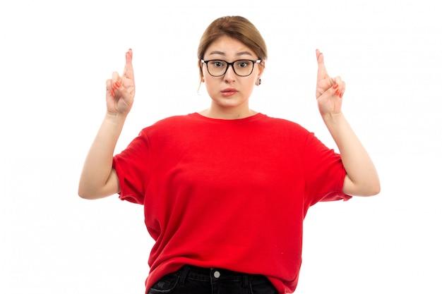 Een vooraanzicht jong aantrekkelijk meisje in rode t-shirt die zwarte jeans in zonnebril dragen die op het wit stellen Gratis Foto