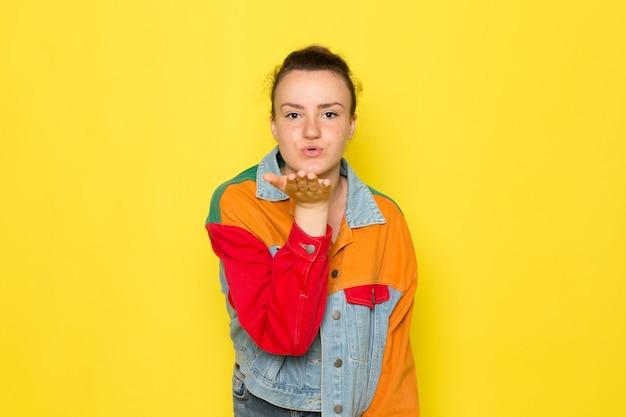 Een vooraanzicht jong wijfje in geel overhemd kleurrijk jasje en jeans die en luchtkussen stellen verzenden Gratis Foto